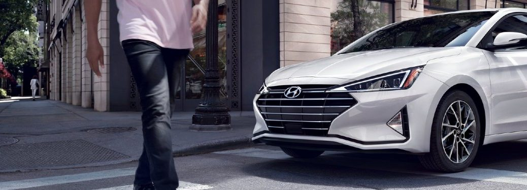 Man crossing the street in front of a white 2020 Hyundai Elantra