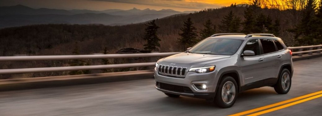 2020 Jeep Cherokee driving down a rural highway road