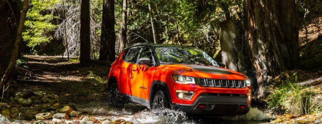 2020 Jeep Compass driving through the water in forest