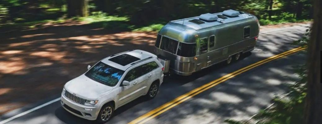 2021 Jeep Grand Cherokee driving and pulling a trailer