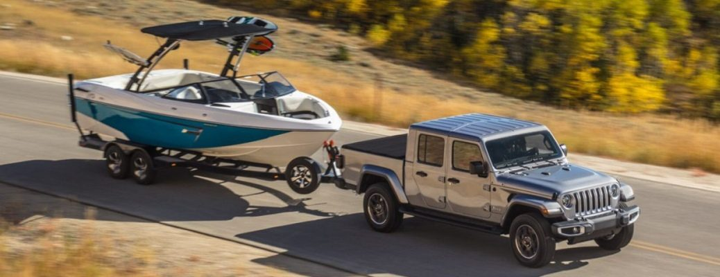2020 Jeep Gladiator silver towing a boat side view