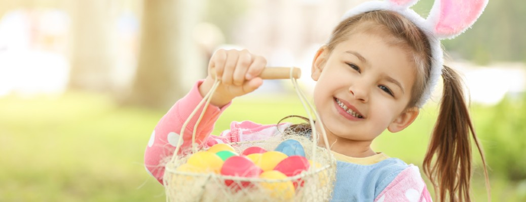 A little girl smiling with bunny ears on while holding an easter basket in a grassy area.