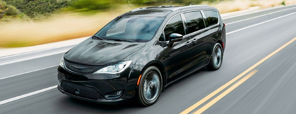 A black 2020 Chrysler Pacifica driving quickly down an open highway.