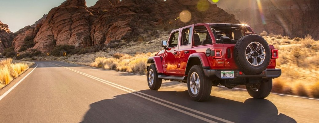 The rear and side view of a red 2020 Jeep Wrangler with the hard top off driving down an open road.