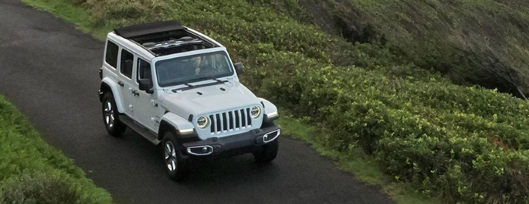 A white 2020 Jeep Wrangler driving down a dirt road.