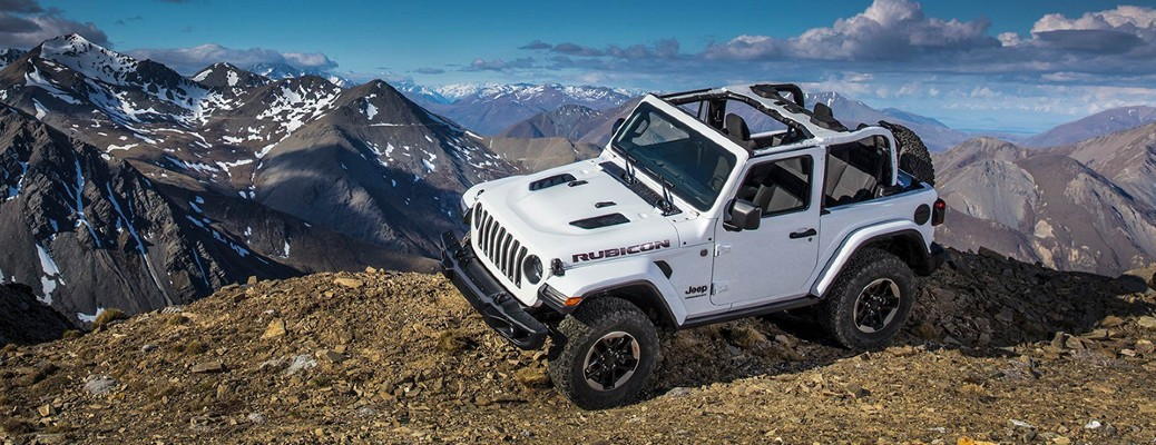 A white 2019 Jeep Wrangler driving in front of a mountain scene.