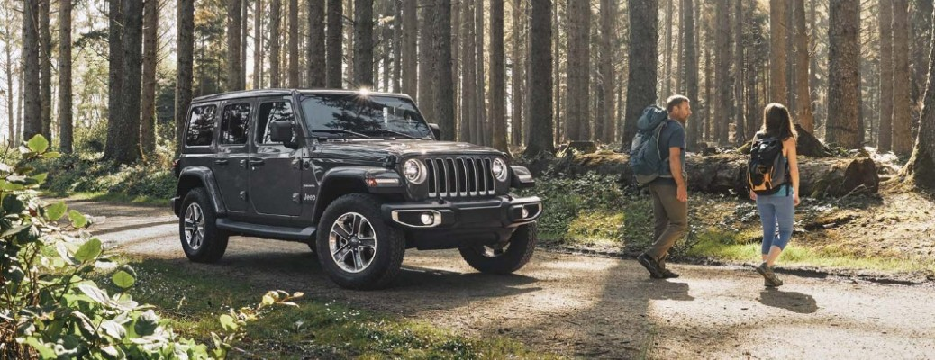 A black 2020 Jeep Wrangler parked off-road with two people going for a hike.