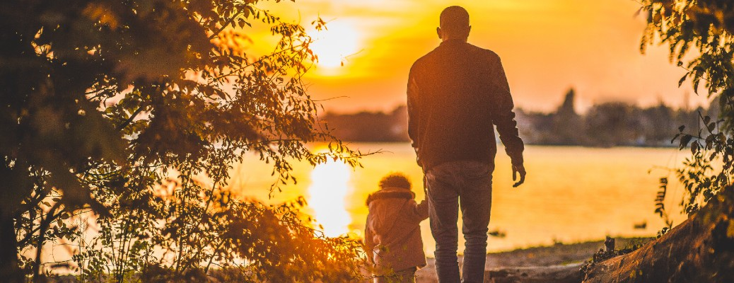 A father and younger child walking towards a lake at sunset.