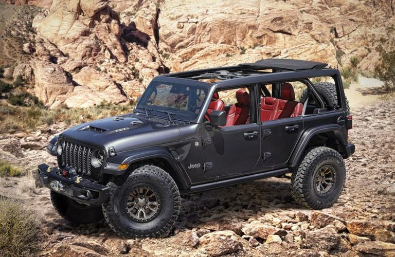 A black 2021 Jeep Wrangler Rubicon 392 Concept vehicle parked in rocky terrain.