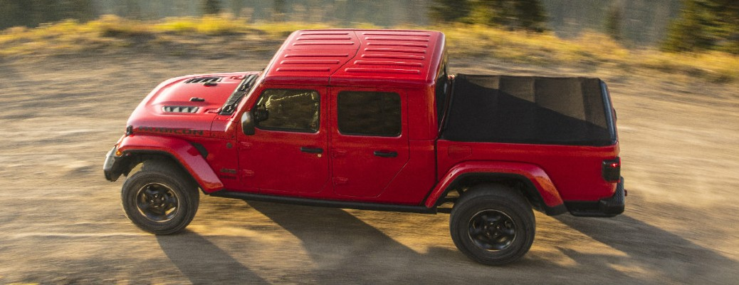 The top side view of a red 2020 Jeep Gladiator driving down a dirt road.