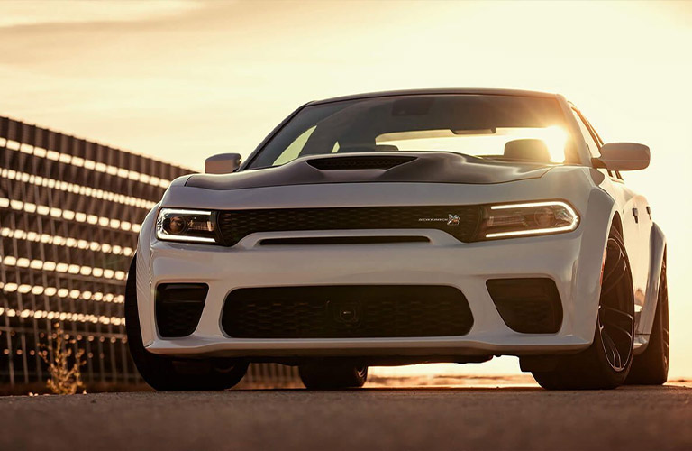 A white and black 2020 Dodge Challenger parked during sunset.