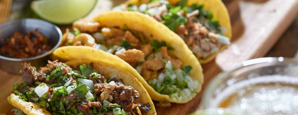 Three street tacos served with other Mexican side dishes.