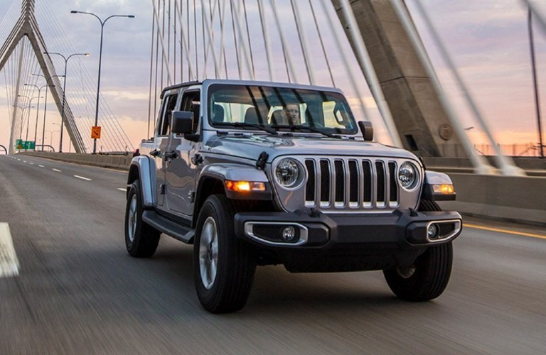 The front view of a gray 2021 Jeep Wrangler 4xe driving on a bridge.