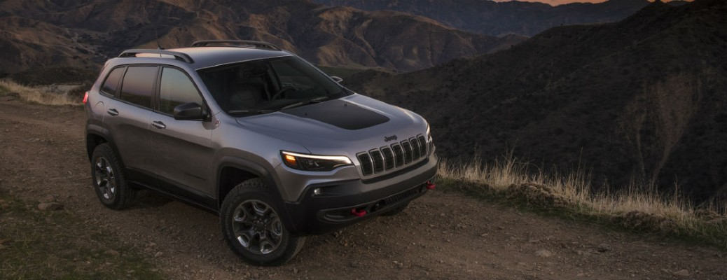 The front and side view of a 2021 Jeep Cherokee driving off-road.