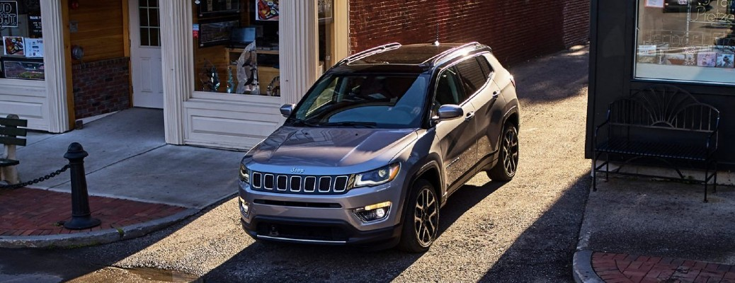 The front of a gray 2021 jeep Compass pulling out of a driveway.