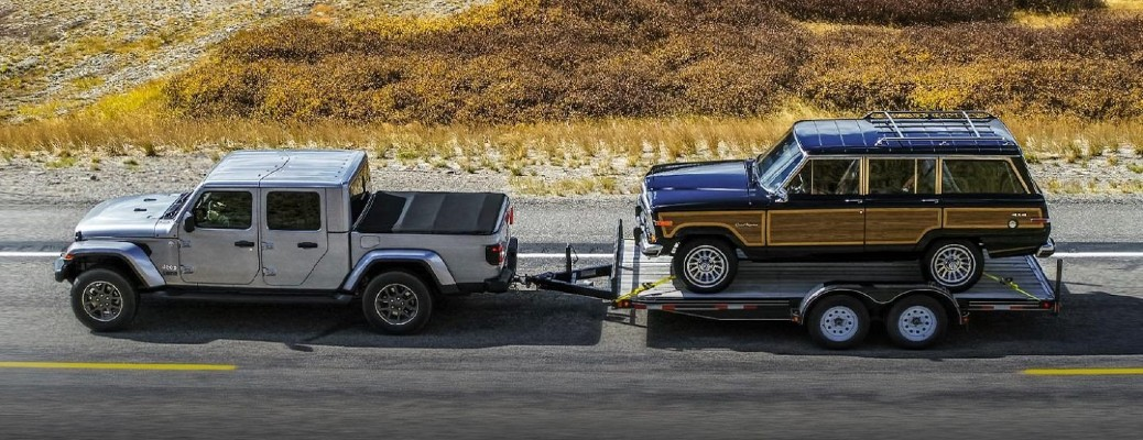 The side view of a gray 2021 Jeep Gladiator hauling an older vehicle on a trailer.