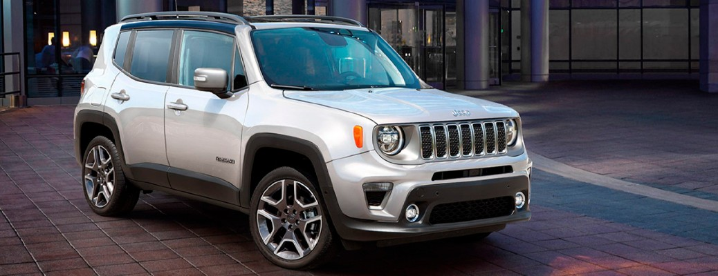 A front and side view of a white 2021 Jeep Renegade parked in a city square.