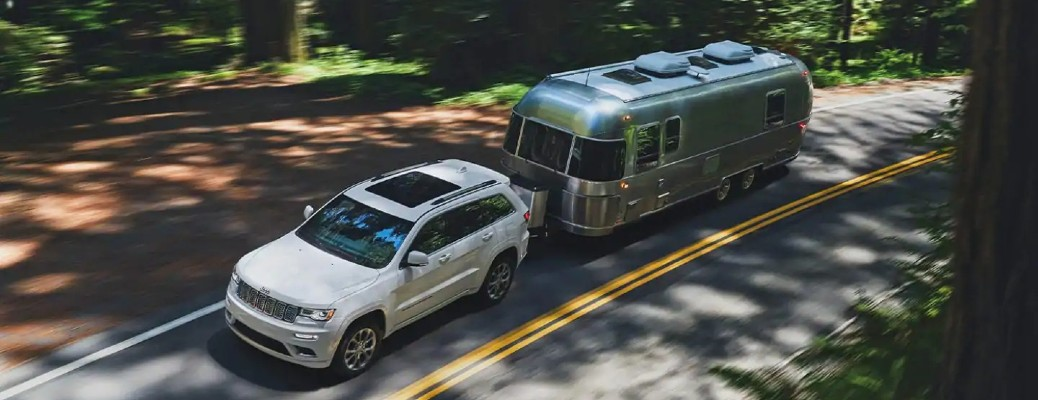 The top view of a white 2021 Jeep Grand Cherokee hauling an Airstream travel trailer.
