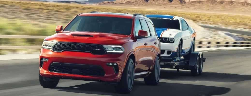 A red 2021 Dodge Durango hauling a Dodge Challenger on a trailer.