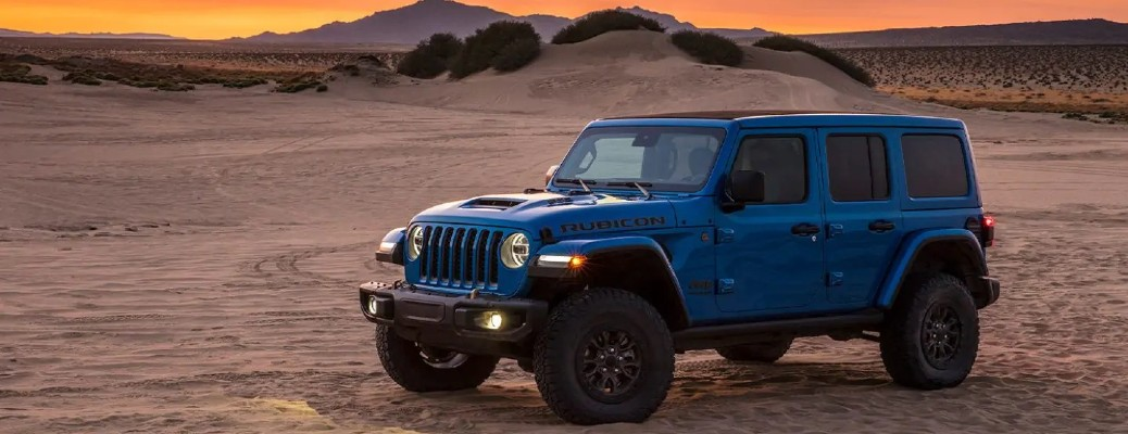 The side view of a blue 2021 Jeep Wrangler parked in a sandy area during sundown.