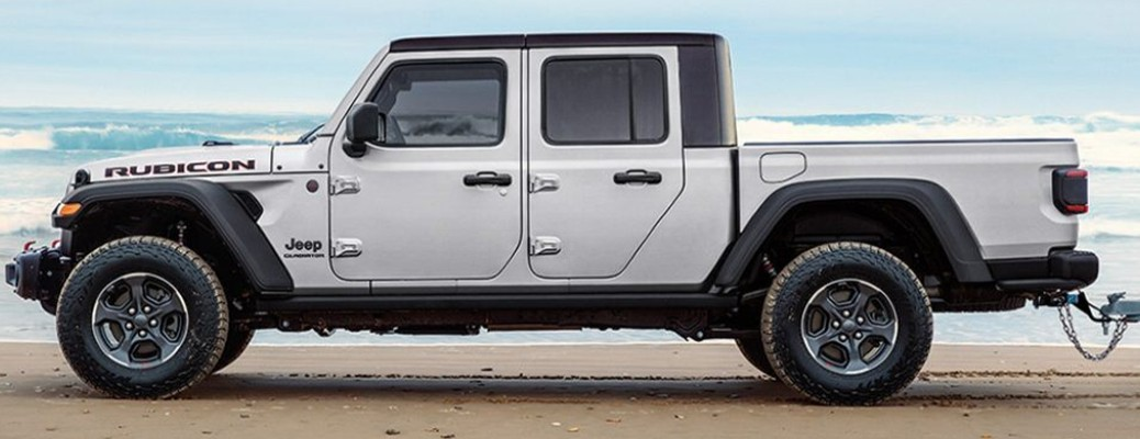 A white-colored 2021 Jeep Gladiator parked on a beach