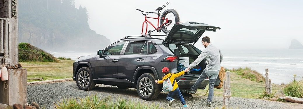 Rear driver angle of a father and son behind the 2020 Toyota RAV4 with the back open and a bike loaded on the roof