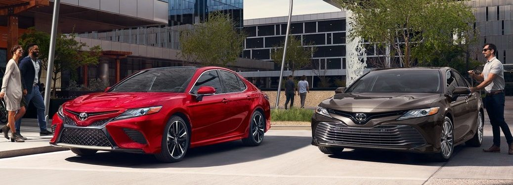 Red 2020 Toyota Camry parked next to a gray 2020 Toyota Camry