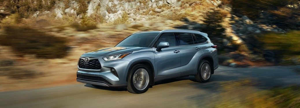 Front driver angle of a blue 2020 Toyota Highlander driving on a rural road