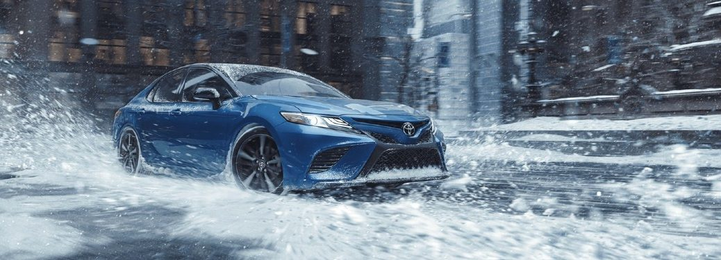 Blue 2020 Toyota Camry driving in the snow