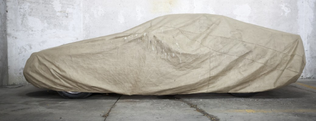 A vehicle covered with an aged tan cover inside a garage.