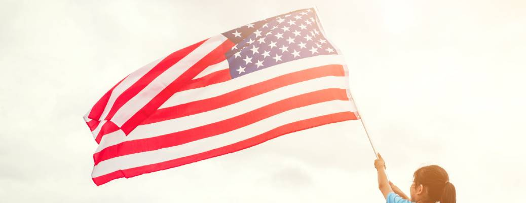 A small child waving an American flag in the air.