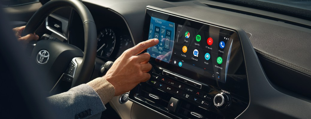 A man touching the inotainment system inside a 2020 Toyota Highlander.
