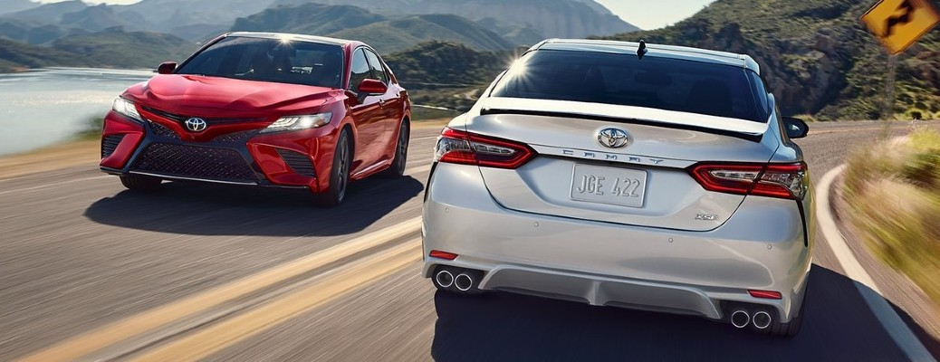 A red 2020 Toyota Camry and a gray 2020 Toyota Camry driving past one another on an open road.