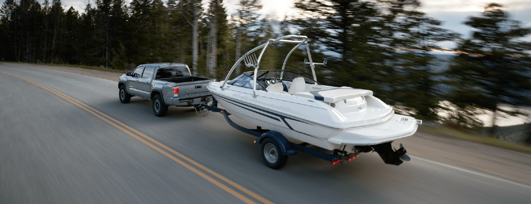 A 2020 Toyota Tacoma hauling a large boat down a wooded road.