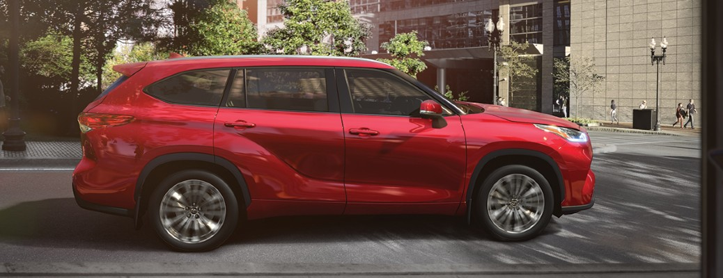 The side view of a red 2020 Toyota Highlander parked along a city road.