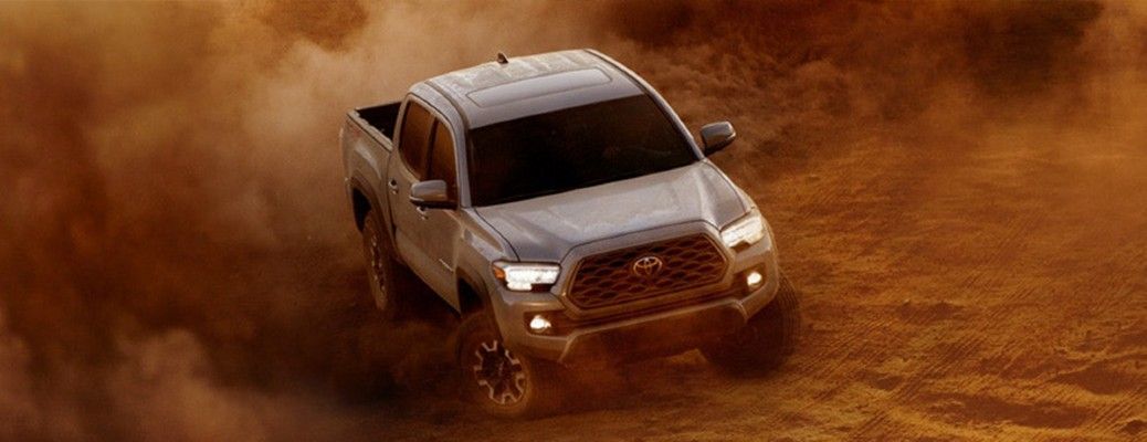 A white 2020 Toyota Tacoma driving through a patch of red sand and kicking up the dirt.