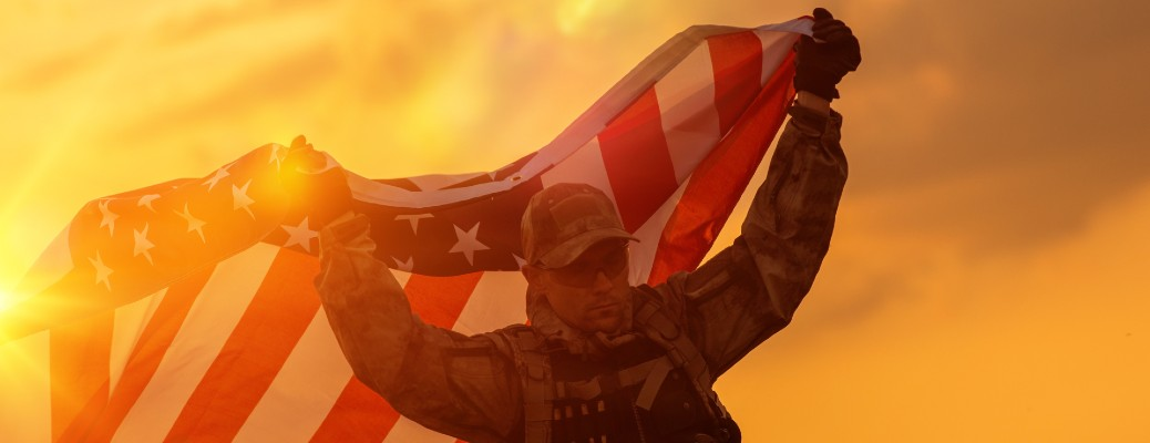An American soldier holding the American flag over his head during sundown.