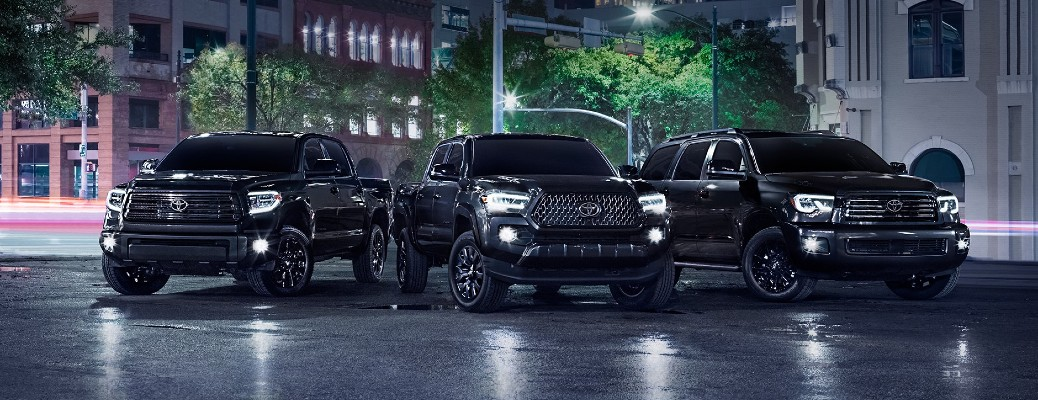 The 2021 Toyota Tundra, Tacoma, and Sequoia Nighsthade Special Edition models parked at night with their lights on.