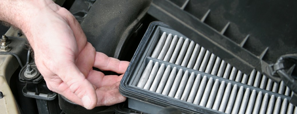 A hand taking out a dirty cabin air filter inside a vehicle.
