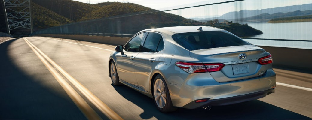 The rear and side view of a gray 2020 Toyota Camry driving quickly down a highway.
