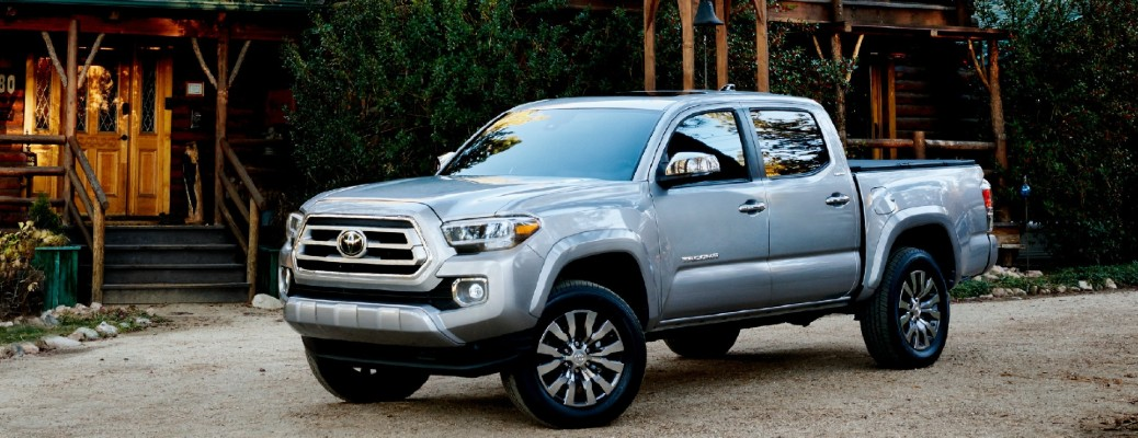 A gray 2021 Toyota Tacoma parked near a large cabin.