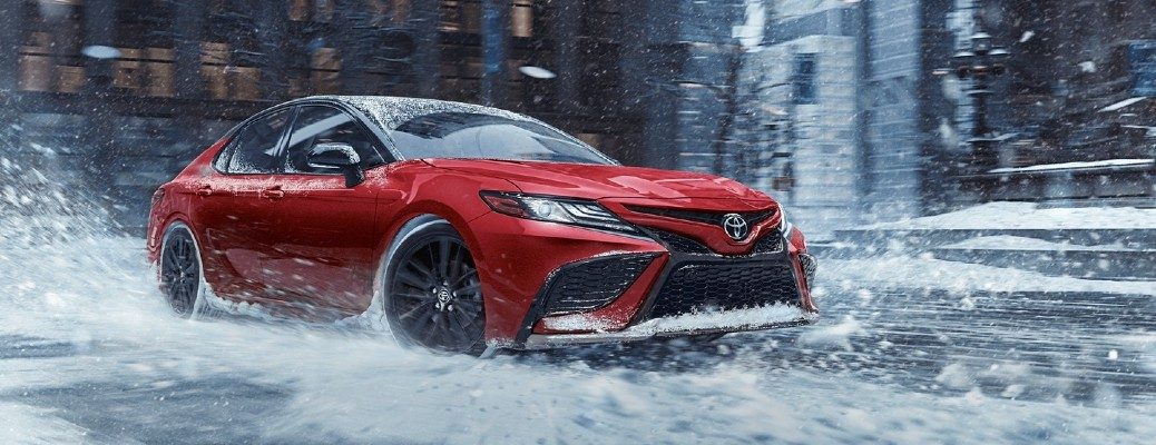 The front and side view of a red 2021 Toyota Camry driving in wintry conditions.