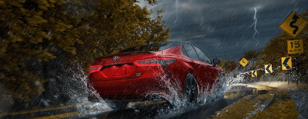 The rear view of a red 2021 Toyota Camry driving in a storm.