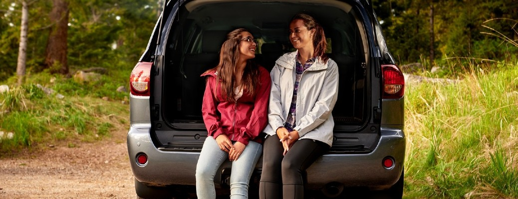 Two young women sitting and smiling at each other in the back of a blue 2021 Toyota Sequoia.