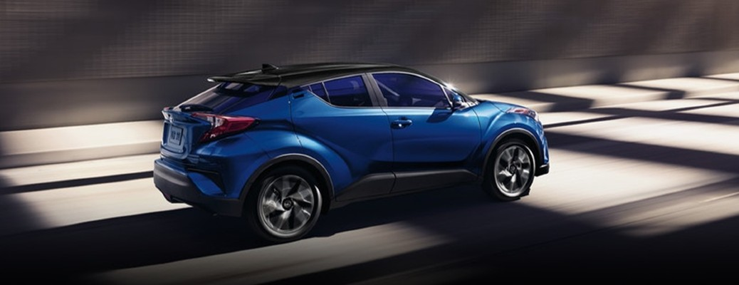 The side view of a blue 2021 Toyota C-HR driving in a tunnel.