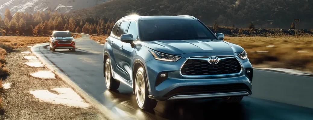 A blue 2021 Toyota Highlander driving down a road in front of a red 2021 Toyota Highlander.