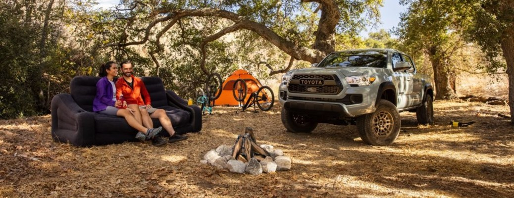 A family unpacked for a camping trip next to their gray 2022 TOyota Tacoma 4X4 Trail Edition.