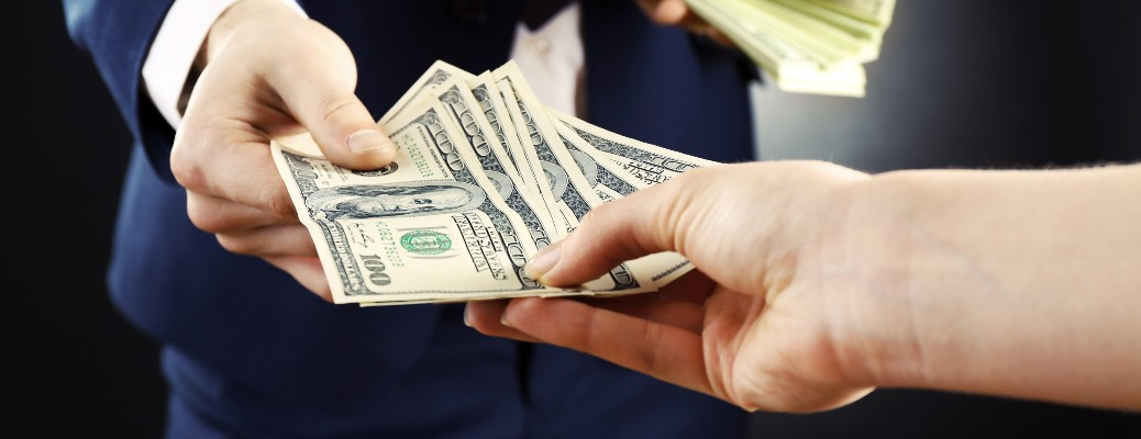 A business person handing money off to a customer.