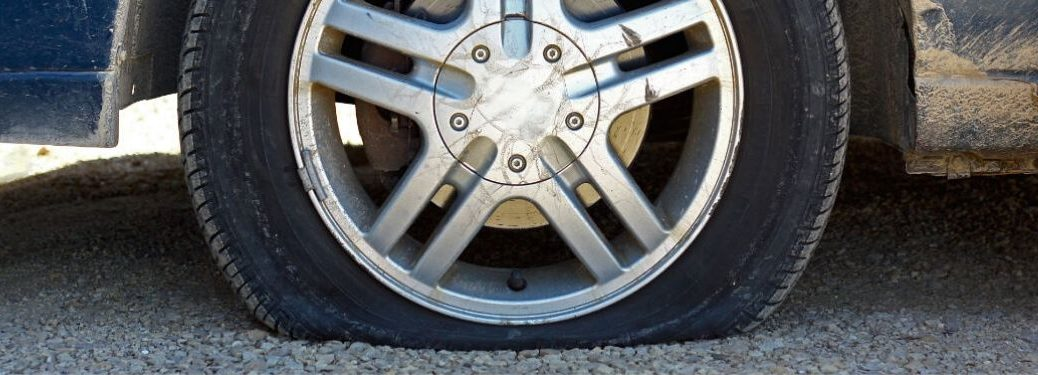 Close-up of a flat tire on a gravel road