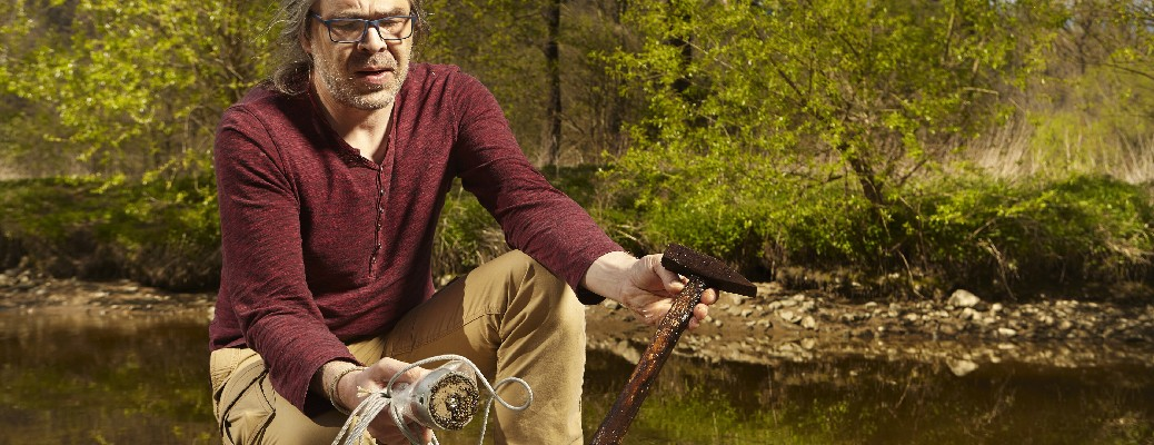 A man examines a rusty hammer he caught while magnet fishing